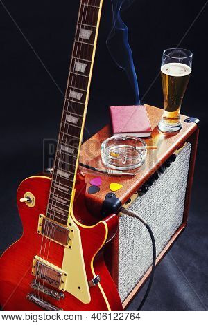 Combo Amplifier For Guitar With Guitar, Glass Of Beer And Smoking Cigarette On The Black Background.