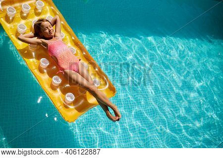 Little Girl Relaxing In Swimming Pool, Enjoying Suntans, Swims On Inflatable Yellow Mattres
