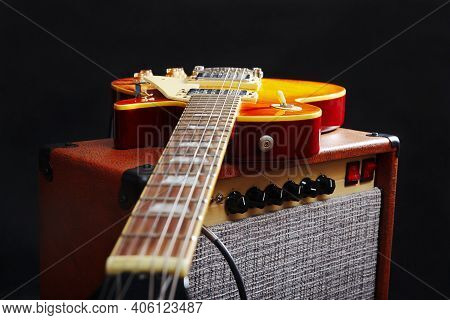 Brown Amplifier For Electric Guitar With Honey Sunburst Guitar On The Black Background.