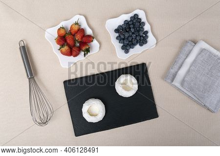 Ingredients For Meringue Cakes With Berries And Whisk. Cake Anna Pavlova. Top View