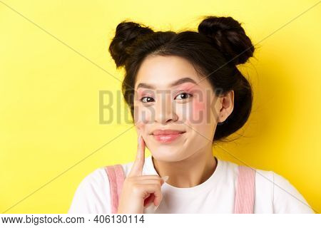 Beauty. Stylish Asian Girl With Bright Glamour Makeup, Touching Soft And Shiny Facial Skin, Smiling