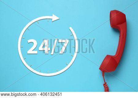24/7 Hotline Service. Red Handset On Light Blue Background, Top View
