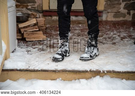 A Young Person In Snow Covered Boots Stands On Snowy Porch By A Pile Of Freshly Chopped Firewood. Wi