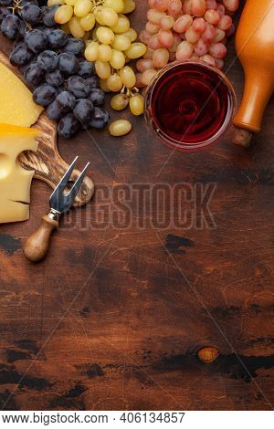Wine bottle, grapes, cheese and glass of red wine. Top view flat lay with copy space