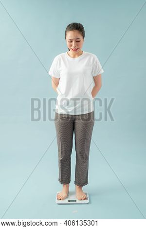 Sad Young Woman Standing On Scale. She Is Not Satisfied With The Result. Diet And Healthy Living Con