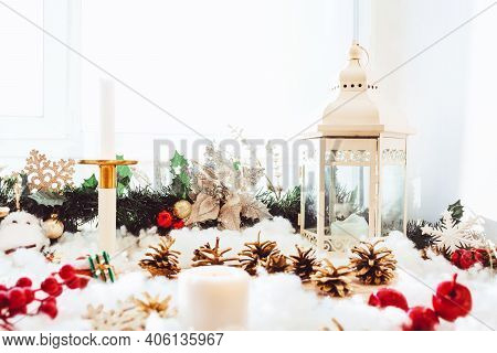 Light Christmas Background With Lantern, Pine Cones, Candles And Red Berries. Window Sill Decoration