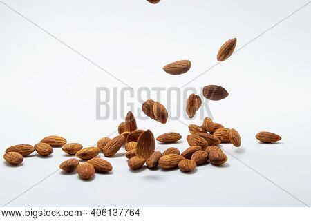 Almonds On A White Background. Isolated Almonds. Roasted Almonds Fall On A White Surface