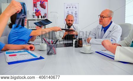 Group Of Medical Staff Discussing In Hospital Meeting Room About Patient Radiography. Clinic Expert