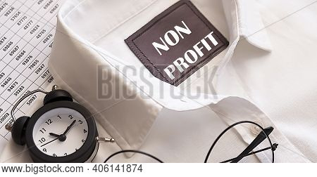 Business Concept. Text Non Profit Written On The Shirt With Alarm Clock And Glasses