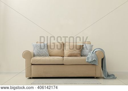Comfortable Sofa Near Beige Wall In Living Room Interior. Space For Text