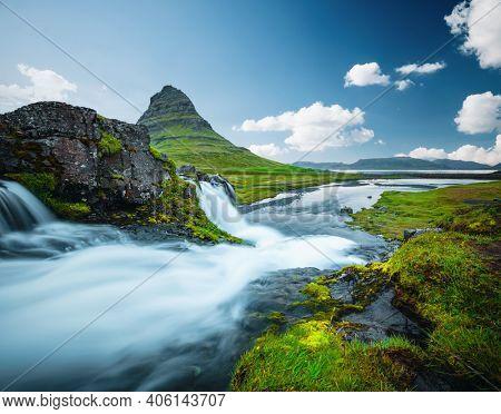 Captivating view of the Kirkjufell volcano. Location place Kirkjufellsfoss waterfall, Iceland, Europe. Image of popular world landmarks. Vibrant photo wallpaper. Discover the world of beauty.