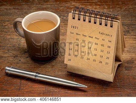 February  2021- spiral desktop calendar with a cuo of coffee on rustic, weathered wood,  time and business concept