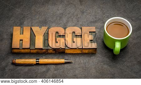 hygge word in vintage letterpress wood type blocks against handmade bark paper with a cup of coffee, Danish cozy lifestyle concept