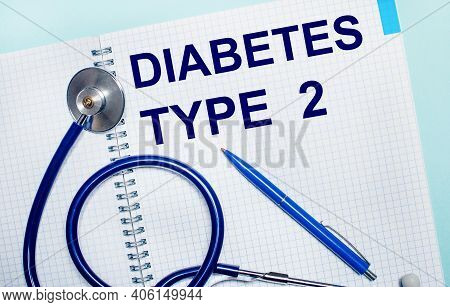 On A Light Blue Background, An Open Notebook With The Words Diabetes Type 2, A Blue Pen And A Stetho