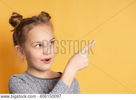 Close Up Of Thoughtful Little Girl Looking To The Side And Pointing Finger To Free Space For Text. C