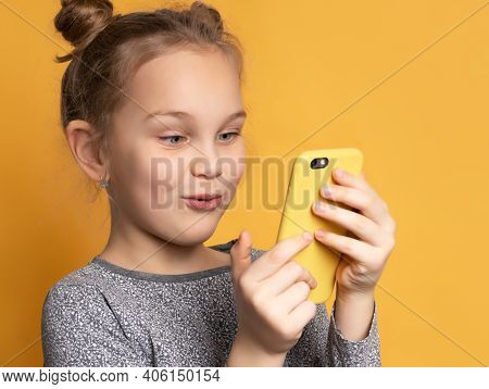 Attractive Little Blonde Girl Looking At Her Mobile Phone Screen With Joyful Face, On Yellow Backgro