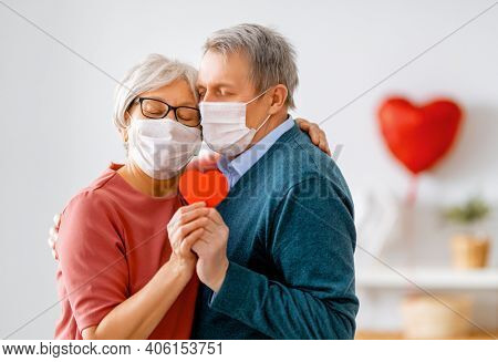 Elderly couple on valentine's day. Joyful nice senior woman and her husband are wearing facemasks.