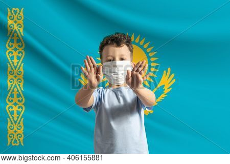 Little White Boy In A Protective Mask On The Background Of The Flag Of Kazakhstan Makes A Stop Sign