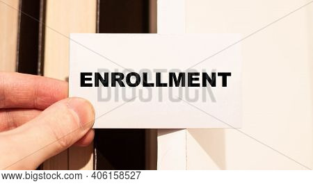 A Businessman Holds His Business Card With The Word - Enrollment On A Book Background.