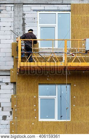 The Builder Insulates The Facade Of A House Under Construction With Mineral Insulation Around The Wi