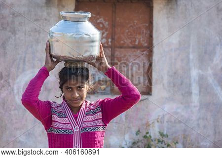 Tikamgarh, Madhya Pradesh, India - January 23, 2021: An Unidentified Indian Village Girl Carry Water