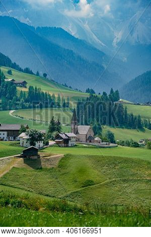 View Of Santa Maddalena Church In Dolomites, Italian Alps. Val Di Funes Valley . Lonely Church On Gr