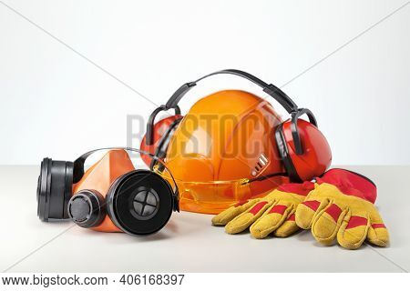 Personal Protection Equipment, Respiratory, Helmet, Headphones, Glasses And Glove On Gray Surface.