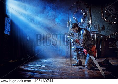 Medieval knight in armor makes an oath of allegiance by kneeling and bowing his head on the sword in the castle before the battle.