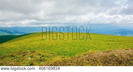 Mountain Landscape In Summer On A Cloudy Day. Grass Covered Hillside Meadow. Carpathian Watershed Ri
