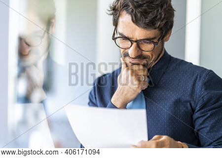 Business Man Wearing Glasses  Holding Paper Document. Successful Male Portrait Thinking And Reading