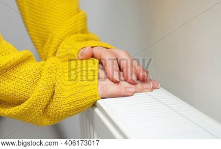 The woman warms her hands on the radiator