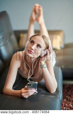 Beautiful girl relaxing at home listening to pleasant music in headphones.
