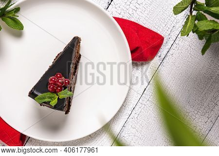 Slice Of Chocolate Cake Called Mozart Decorated With Glazed Red Currant Berries And Mint Leaf On Whi