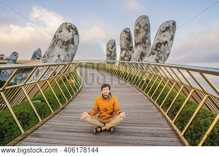 Young Man Tourist Doing Yoga On A Famous Tourist Attraction - Golden Bridge At The Top Of The Ba Na