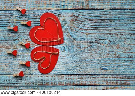 Two Wooden Red Hearts Are Beautifully Placed On A Turquoise Vintage Wooden One. With Place For Text
