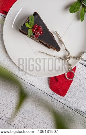 Chocolate Cake Called Mozart Decorated With Glazed Red Currant Berries And Mint Leaf On White Plate