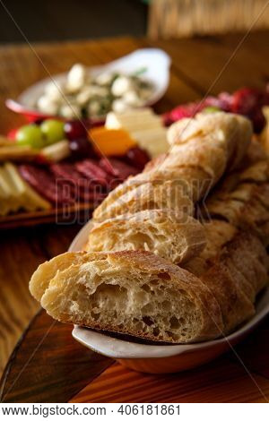 Crusty Italian Bread With Charcuterie Board In Background