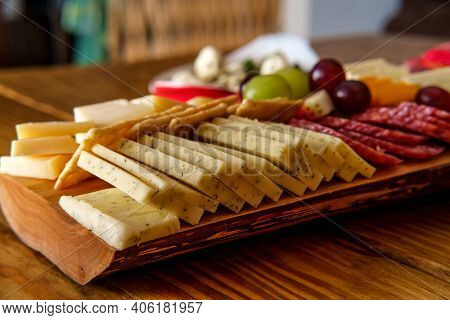 Italian Charcuterie Board Featuring Crackers Cheese And Salami Served On Wooden Plank With Raw Bark