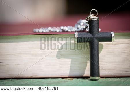 Closeup Of Simple Wooden Christian Cross Necklace On Bible. Concept For Christian, Christianity, Cat