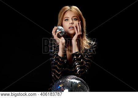 Surprised Model Posing On Near Disco Ball. Gorgeous Curly Blonde Woman In A Black Sequins Dress For