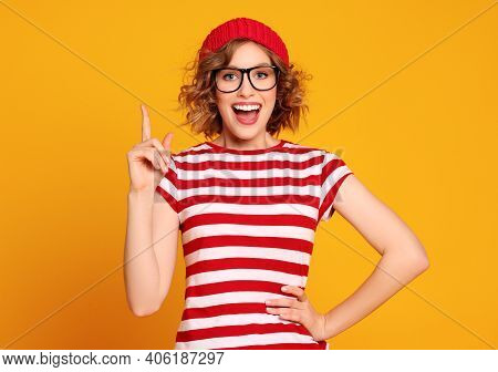 Cheerful Young Female With Hand On Waist Smiling For Camera And Pointing Up While Having Idea Agains