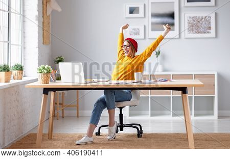 Full Body Delighted Young Woman Smiling And Stretching Raised Arms While Sitting On Chair After Fini