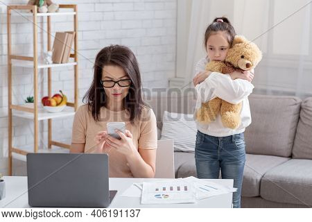 Lonely Teen Girl Hugging Teddy Bear While Her Busy Mom Working Online From Home, Not Paying Attentio