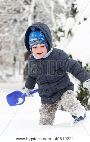 Little Boy With Shovel Playing In Snow