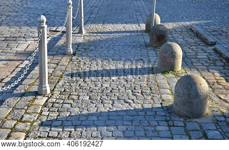 Stone Barriers In A Square Shaped Cylinder With A Hemisphere On Top. Granite Curbs As Stops At The P