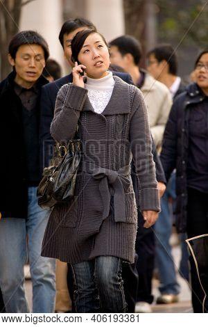 Shanghai, China, Asia - November 29, 2008: Young Chinese Woman Talking By Cell Phone At Nanjing Road