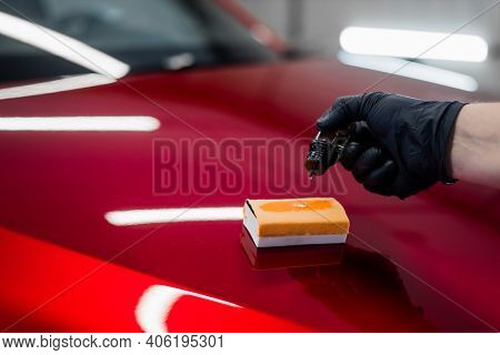 Close-up Of A Man Hand Dripping Liquid Coating On A Sponge Applicator On A Car Bonnet. Preparing For