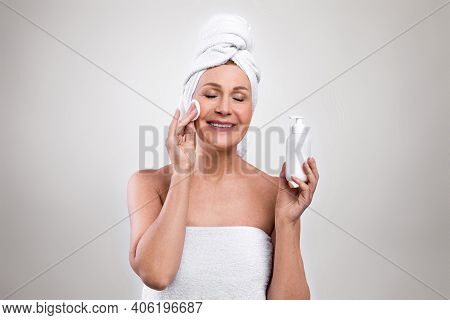 Attractive Senior Woman Wearing Bath Towels, Enjoying Her Beauty And Face Care Routine, Applying Nat