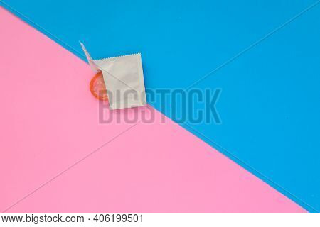 Top View Of Opened Condom And Red Condom In Pack On Blue And Pink Color Paper Background With Copy S