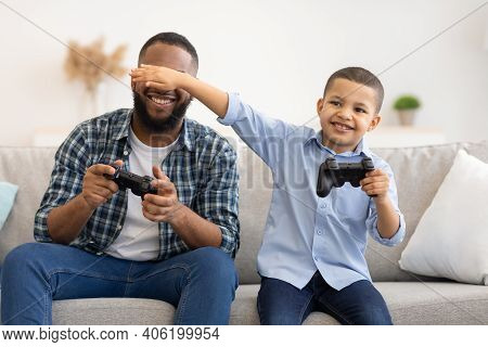 Son Covering Dads Eyes Playing Video Games Together Sitting On Sofa Indoors. Young Father And Male K